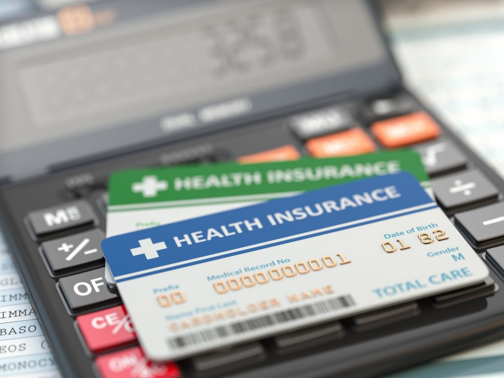 Medical insurance cards on the calculator. Health care costs con