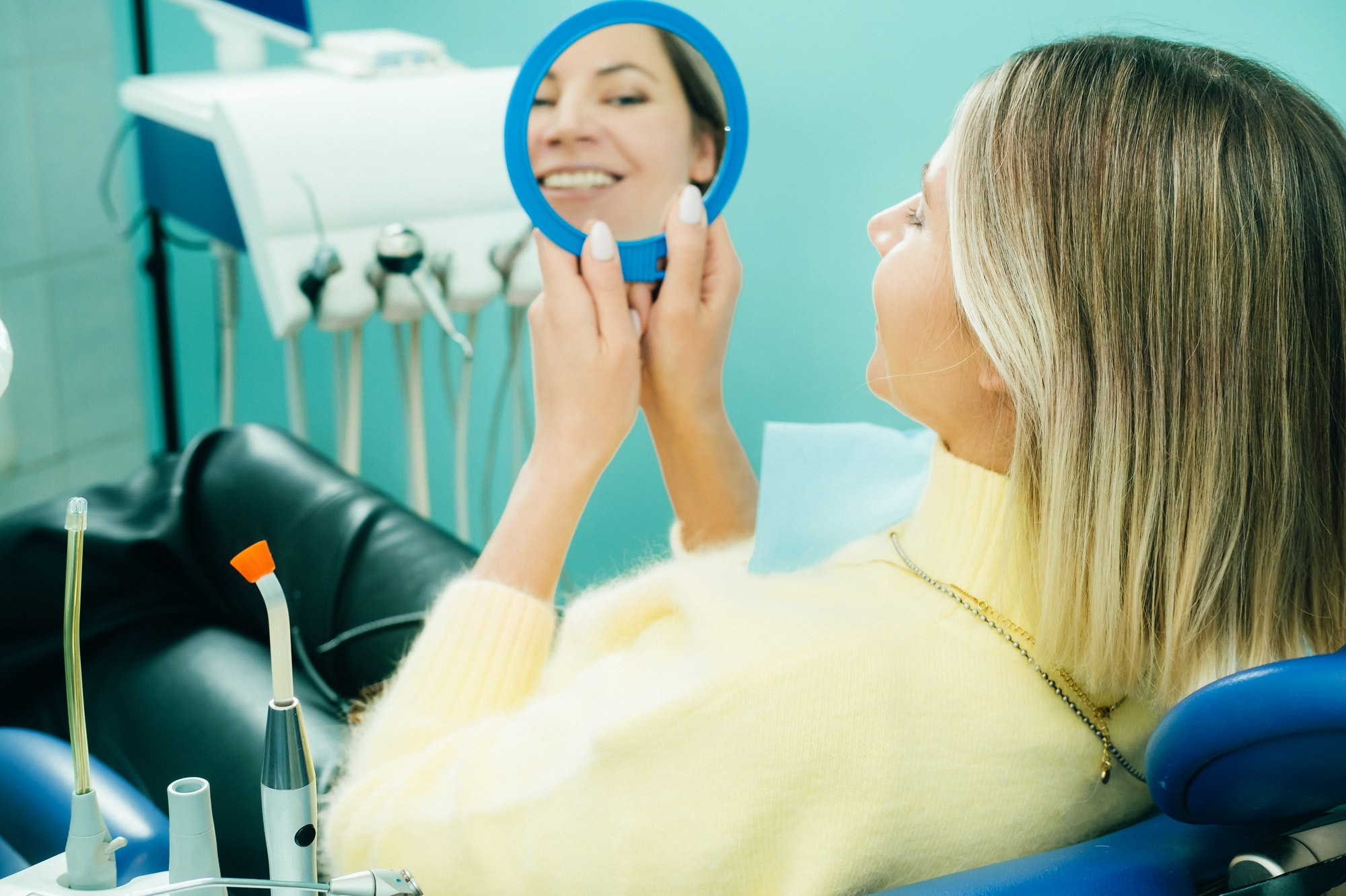 The girl smiles and looks in the mirror in dentistry