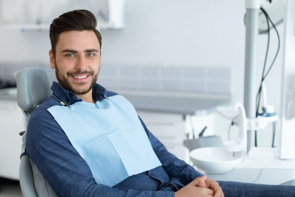 Young man patient smiling in dentistry, copy space